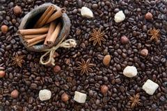 Feijões de café, açúcar de bastão, varas de canela em um jarro, inverno fotografia de stock