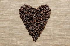 Feijões de café arranjados em uma forma do coração Foto de Stock