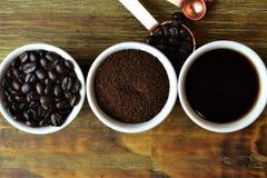Feijões de café, café à terra, e café preto nos copos brancos Foto de Stock