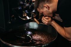 Feijões de café de cheiro do homem fotografia de stock royalty free