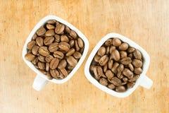 Feijões de café claros do marrom do assado em dois copos de café branco Imagem de Stock Royalty Free