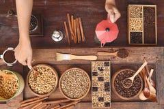 Feijões de café com café à terra na colher e na canela de madeira, chaleira vermelha Fotografia de Stock