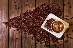 Feijões de café com café na tabela Imagens de Stock Royalty Free