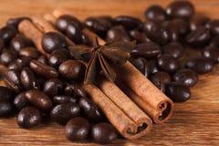 Feijões de café com canela e anis na tabela de madeira fotos de stock