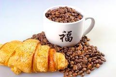Feijões de café com copo e croissant Foto de Stock
