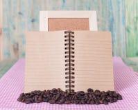 Feijões de café com livro de nota Imagem de Stock Royalty Free