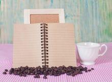 Feijões de café com livro de nota Fotografia de Stock