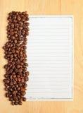 Feijões de café com papel para notas Fotografia de Stock Royalty Free