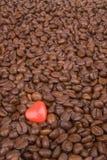 Feijões de café com um coração vermelho do Valentim Fotos de Stock
