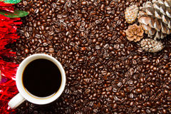Feijões de café & copo de café com cones do pinho da beira do feriado Fotografia de Stock