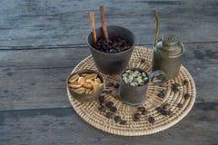 Feijões de café crus e roasted com o copo de bronze na tabela de madeira Imagens de Stock Royalty Free
