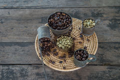 Feijões de café crus e roasted com o copo de bronze na tabela de madeira Imagem de Stock Royalty Free