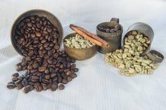 Feijões de café crus e roasted com o copo de bronze no linho de tabela branco Imagens de Stock Royalty Free