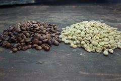 Feijões de café crus e roasted na tabela de madeira Fotografia de Stock Royalty Free