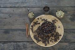 Feijões de café crus e roasted no copo de bronze e no recipiente mau Fotografia de Stock