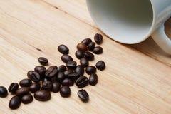 Feijões de café da caneca de café na madeira da tabela Imagens de Stock Royalty Free