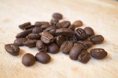 Feijões de café da goma-arábica na superfície de madeira Imagem de Stock