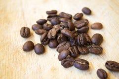 Feijões de café da goma-arábica no fundo de madeira Imagens de Stock Royalty Free