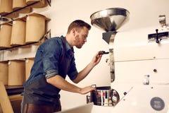 Feijões de café da repreensão do proprietário empresarial com uma máquina moderna Foto de Stock