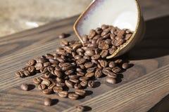 Feijões de café derramados em uma tabela de madeira fotografia de stock royalty free