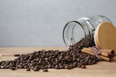 Feijões de café derramados para fora de vidro pouco frasco Imagem de Stock