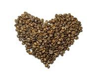 Feijões de café derramados sob a forma do coração isolado Imagem de Stock Royalty Free