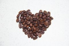 Feijões de café derramados Café sob a forma dos corações fotografia de stock