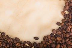 Feijões de café dispersados no papel velho Fotografia de Stock