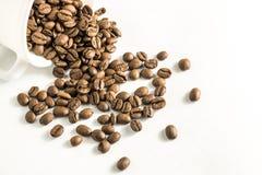 Feijões de café dispersados de um copo em um fundo branco fotografia de stock