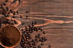 Feijões de café e café à terra na tabela de madeira rústica, vista de Imagem de Stock