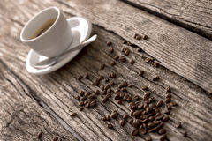 Feijões de café e café em uma tabela rústica Fotos de Stock