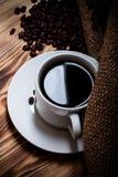 Feijões de café e café no copo branco na tabela de madeira com serapilheira Imagens de Stock Royalty Free