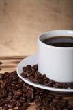 Feijões de café e café no copo branco na tabela de madeira oposto à Fotos de Stock Royalty Free