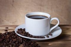 Feijões de café e café no copo branco na tabela de madeira oposto à Foto de Stock