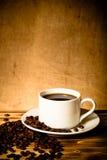 Feijões de café e café no copo branco na tabela de madeira oposto à Imagens de Stock