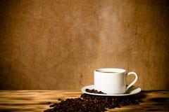 Feijões de café e café no copo branco na tabela de madeira oposto à Imagens de Stock Royalty Free