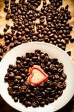 Feijões de café e café no copo branco na tabela de madeira para o backgro Imagem de Stock
