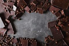 Feijões de café e chocolate escuro Fundo com chocolate Feijões de café Varas de canela e anis de estrela imagem de stock royalty free