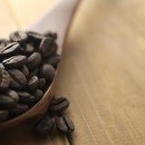 Feijões de café e colher de madeira imagens de stock