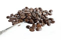 Feijões de café e colher de prata isolados no branco Foto de Stock