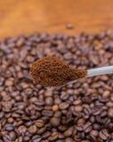 Feijões de café e colher do metal Imagem de Stock