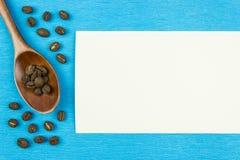 Feijões de café e colher de madeira em um fundo azul fotos de stock