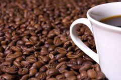 Feijões de café e copo de café imagem de stock