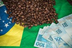 Feijões de café e dinheiro brasileiro na bandeira de Brasil Foto de Stock