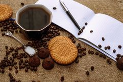 Feijões de café e doces de chocolate no fim do pano de saco acima Café e fundo dos doces fotos de stock royalty free
