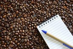 Feijões de café e livro de nota Fotografia de Stock Royalty Free