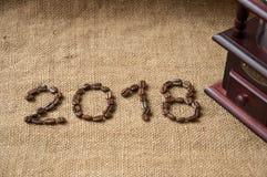 Feijões de café e moedor de café, fim acima no fundo do saco de serapilheira, 2018 anos novos felizes Imagens de Stock