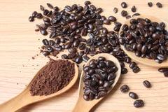 Feijões de café e pó do café na colher de madeira em uma tabela de madeira imagens de stock