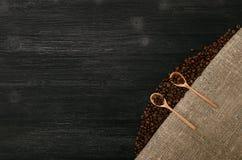 Feijões de café em colheres de madeira das colheres na tabela Imagem de Stock