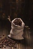 Feijões de café em sacos de serapilheira sobre o fundo de madeira Imagem de Stock Royalty Free